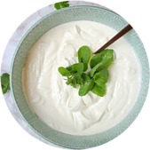 A blue bowl full of Greek yogurt with mint leaves and a spoon