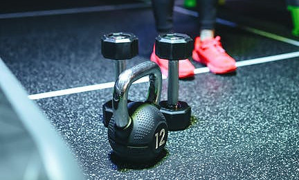 A pair of black and silver dumbbells standing upright behind a black and silver kettlebell