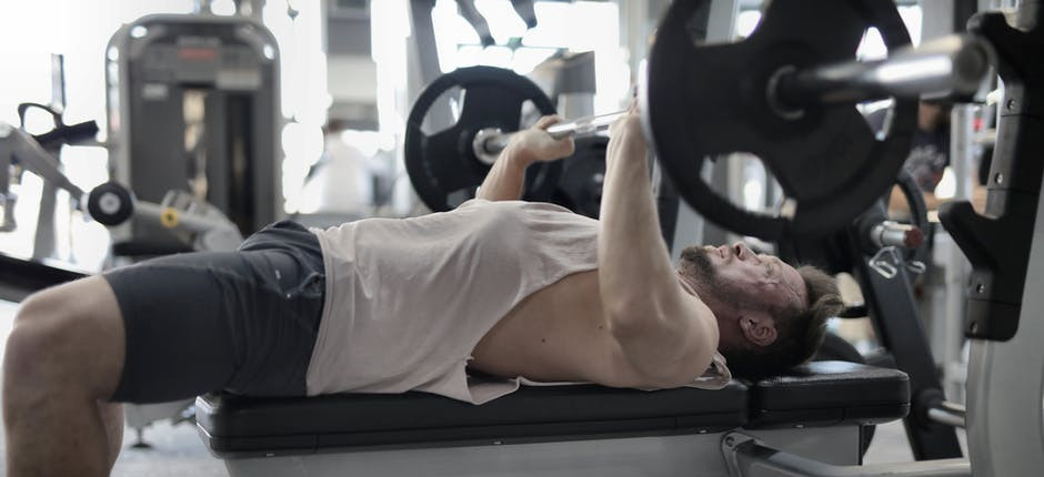 A weight trainer lying flat on a weight bench lifting a barbell