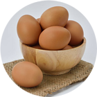 A wooden bowl filled with brown eggs