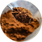 Close up of chocolate protein powder on a spoon above a glass container