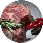 Close up shot of a joint of beef with sprig of rosemary and chillies on a white plate