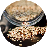 Quinoa being spilled onto a table from a glass container