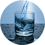 Water being poured into glass sitting on a black surface infront of a blue background