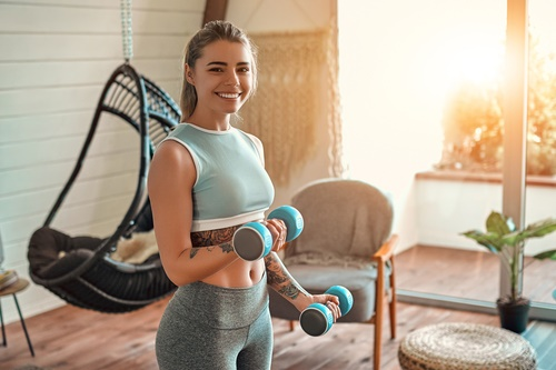 A woman using a pair of blue dumbbells to work out at home