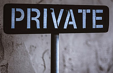 A black sign that reads 'private' in blue lettering in front of a grey cement wall