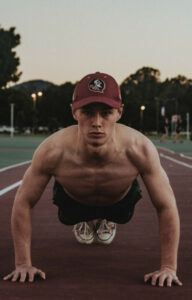 A guy in a baseball cap performing a press up on a running track