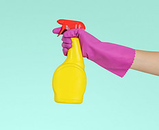 A hand with a purple rubber glove holding a yellow spray bottle with red top on a blue background