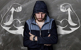 A man in a hoodie standing in front of a black wall with painted flexing arms