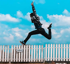 A man jumping over a white picket fence with his hands in the air in front of a blue sky background