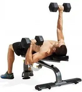 A man lying on a weight bench performing alternating dumbbell presses with a pair of dumbbells