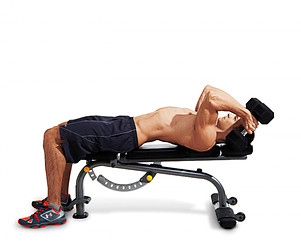A man lying on a weight bench with a pair of dumbbells performing the skullcrusher exercise
