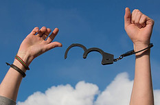 A pair of hands up in the air breaking free of handcuffs