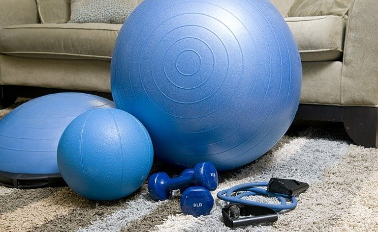 A set of blue coloured gym equipment including dumbbells, resistance band and medicine ball on a grey rug siting in front of a grey sofa