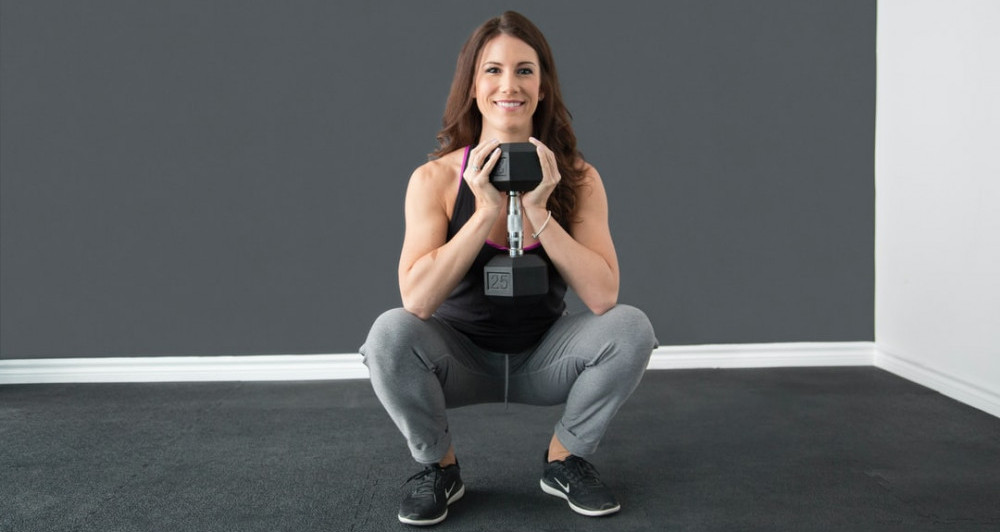 A woman in gym gear holding one dumbbell with both hands performing a squat