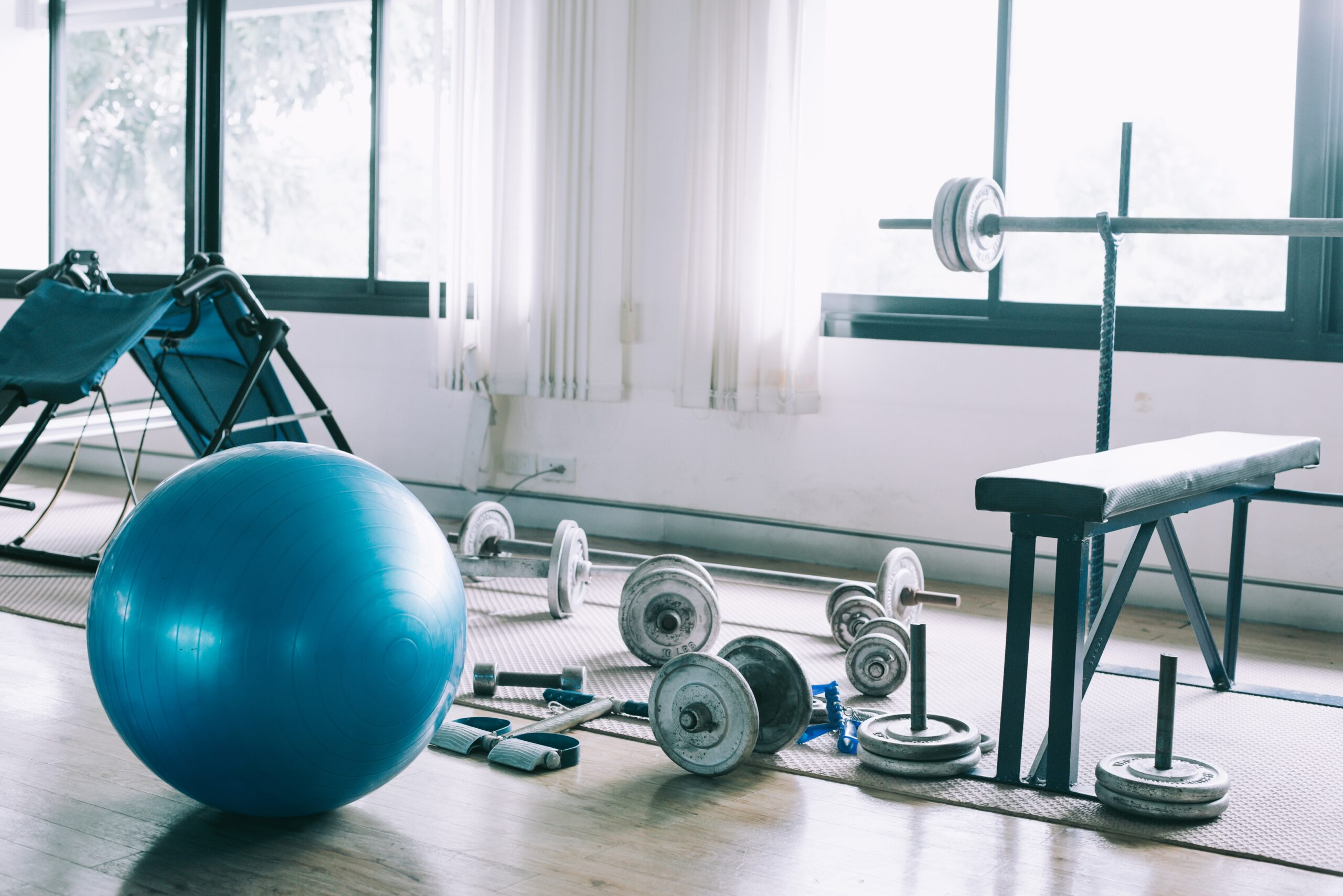 A home gym set up including dumbbells, weight bench and blue medicine ball on a hardwood floor