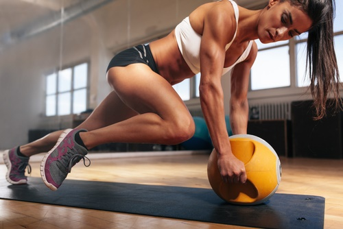 Woman in gym gear working out with a yellow medicine ball on the floor