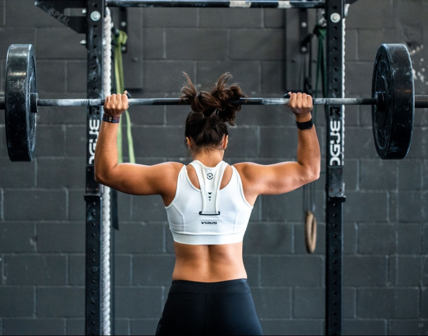 Rear shot of a woman lifting a barbell above her head