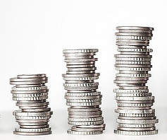 Three stacks of silver coins increasing in height on a white background
