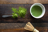 Green-tea-extract-powder-next-to-a-white-cup-of-green-tea