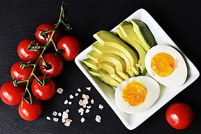 Some-red-vine-tomatoes-next-to-a-plate-of-chopped-avocado-and-boiled-egg-halves-on-a-black-slate