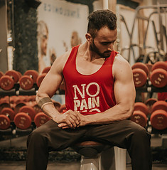 A-man-in-a-red-vest-sitting-on-a-gym-bench-flexing-his-shoulder-muscles