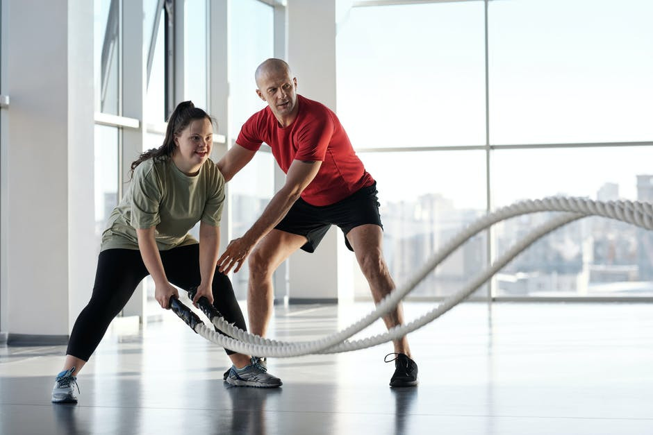 Girl-doing-ropes-exercise-with-personal-trainer