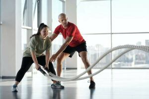 girl-working-out-with-ropes-together-with-personal-trainer