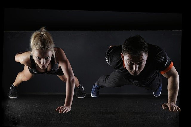 Man-and-woman-performing-one-arm-push-ups