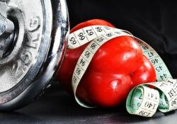 A silver dumbbell and red pepper with measuring tape wrapped around it